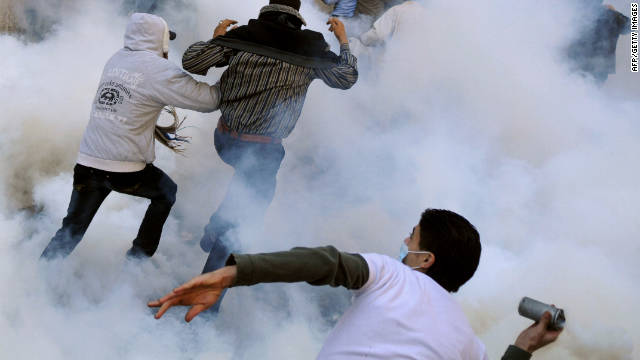 A protester throws a tear gas canister back toward security forces Monday during clashes in Tahrir Square.