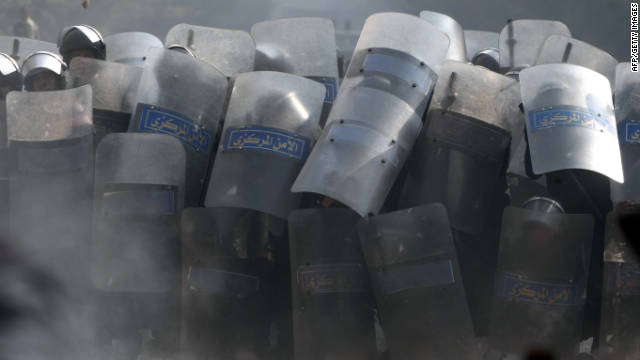 Riot police take cover behind their shields Wednesday during the fifth day of clashes with protesters near Tahrir Square.