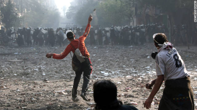 A protester hurls rocks at a line of riot police on Wednesday, November 23, near Tahrir Square in Cairo.