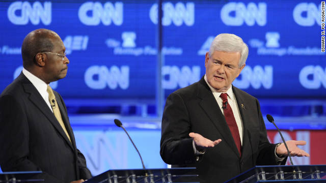 Herman Cain looks on as new GOP frontrunner Newt Gingrich speaks at CNN debate.
