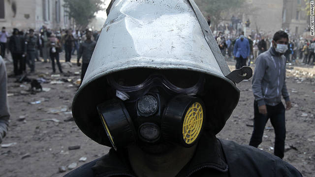 An Egyptian protester uses improvisation to protect his face and head from tear gas during clashes with riot police near Cairo's Tahrir Square on November 23, 2011. 