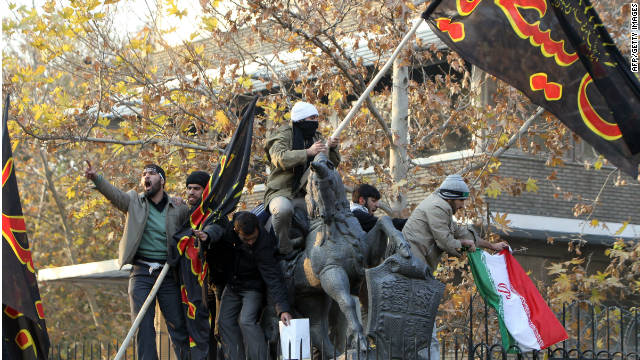 Protesters climb into the UK embassy in Tehran on Tuesday.
