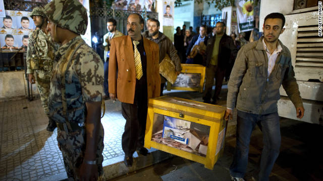Election officials remove ballot boxes from a polling station near Tahrir Square at the end of the voting day in Cairo on Tuesday.