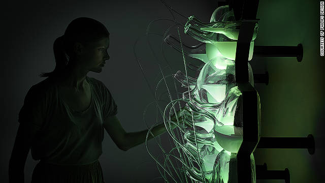 The bio-light concept creates a glowing green light. Hand-blown glass bottles are filled with bioluminescent bacteria which glow green when fed methane gas.