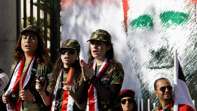 Syrian pro-regime supporters dressed in military uniform stand in front of a mural of President Bashar al-Assad in Damascus on Saturday.