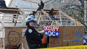 Occupy DC protesters sit atop a wooden structure at their encampment in Washington\'s McPherson Square on Sunday.