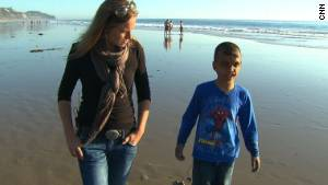 Youssif walks along the California beach with CNN\'s Arwa Damon, who first told the boy\'s story in 2007.