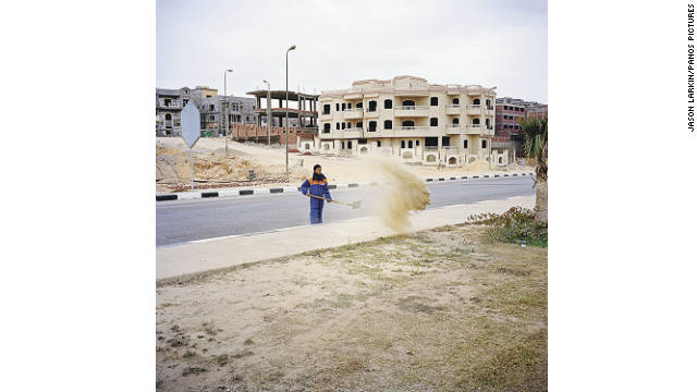 A street cleaner removes sand from the roadside in New Cairo. Each week teams of workers shovel several tons of sand fromthe road network, most of which blows in from the surrounding desert.