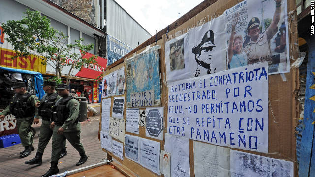 Police in Panama City pass next to a street vendor's stand decorated with pictures and articles of Manuel Noriega on Friday..