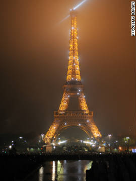 Watch an illuminated Eiffel tower from the River Seine in Paris, France.