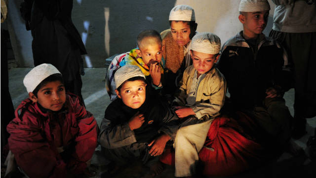 Young students sit in a room after being rescued in a police raid on a madrassa in Karachi late Monday.