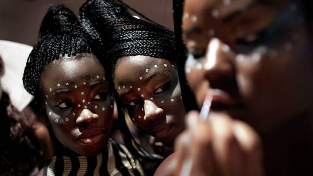 Finishing touches are put on a model's make up as two Kinabuti girls watch in the background.