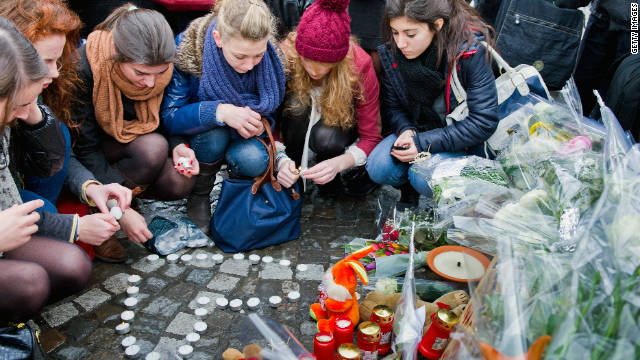 People leave tributes Wednesday at the site of Tuesday's lethal gun and grenade attack in central Liege, Belgium.