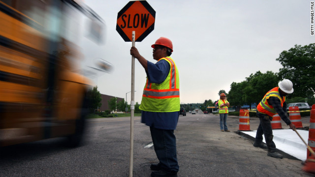 Flagger Darlene Martinez slows traffic next to a road project in Littleton, Colorado, funded by federal stimulus money.