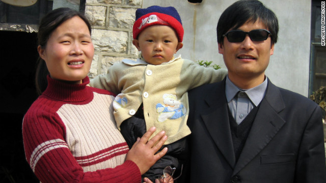 A picture dated March 28, 2005 shows blind activist Chen Guangcheng, right, with his wife and son Chen Kerui outside the home in Dondshigu village, Shandong province.
