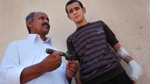 Mohamed and his father Abdul with part of the rifle grenade that exploded in his hand.