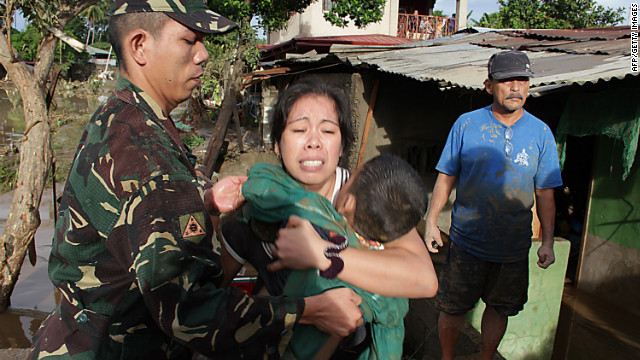 A woman holds the body of her child, who was killed by flooding during the storm.