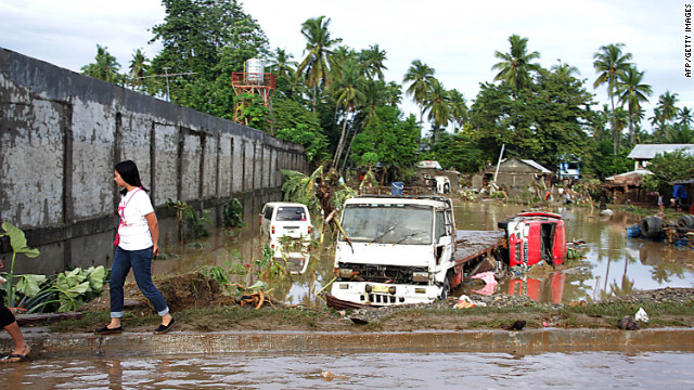 A woman walks past debris and vehicles partially submerged by floodwaters Saturday in Iligan City.