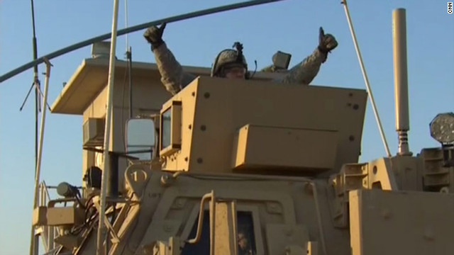 A U.S. soldier gives a thumbs up from the roof of his brigade's Humvee while crossing the Iraq-Kuwait border.
