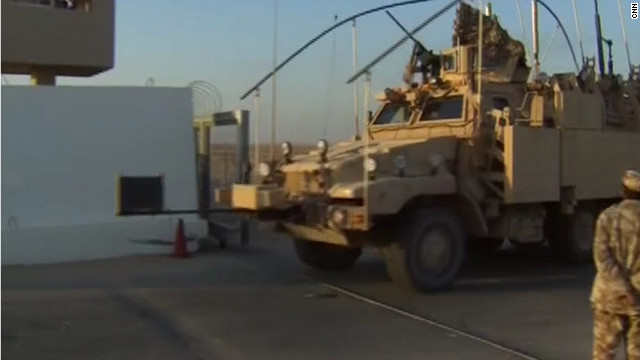 "One of the first U.S. Humvees cross the Iraq-Kuwait border on December 18 to signify the ""tactical road march"" out of the combat zone."