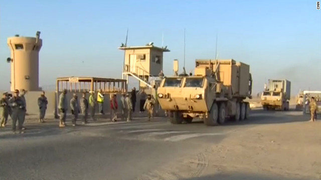 U.S. and Iraqi troops line up as the final U.S. Army convoy crosses the border from Iraq into Kuwait.