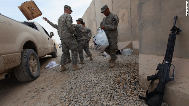 Soldiers from the 3rd Brigade, 1st Cavalry Division toss out trash while preparing to depart in the last convoy from Iraq.