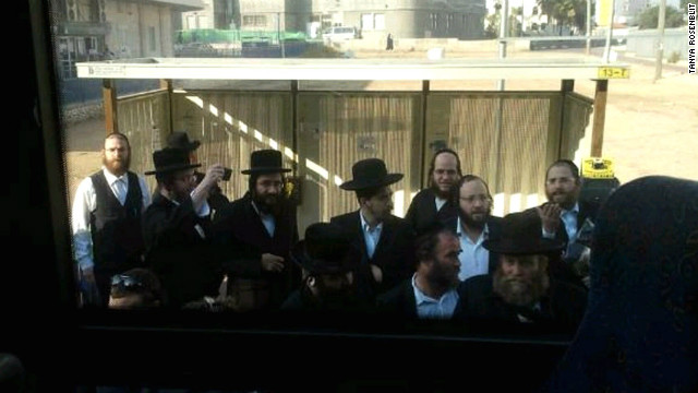 A crowd of ultra-orthodox men gather at a bus stop while Tanya Rosenblit refuses to sit in the back of the bus.