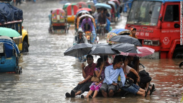 Bangladeshis attempt to stay dry above flood waters in the capital, Dhaka. Bangladesh was ranked the country most vulnerable to climate change, and Dhaka the world's most vulnerable city, due to its exposure to threats such as flooding, storm surge, cyclones and landslides, its susceptible population and weak institutional capacity to address the problem.