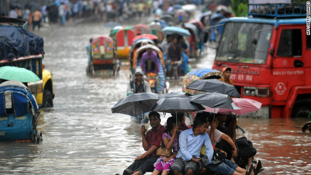 Bangladeshi pedestrians holding umbrellas hitch a ride on a rickshaw van as they attempt to stay dry over flood waters in the Bangladeshi capital of Dhaka on July 28, 2009. The Met Office study predicts that, over the course of the century, an additional five million people in Bangladesh will be displaced by floods caused by climate change.