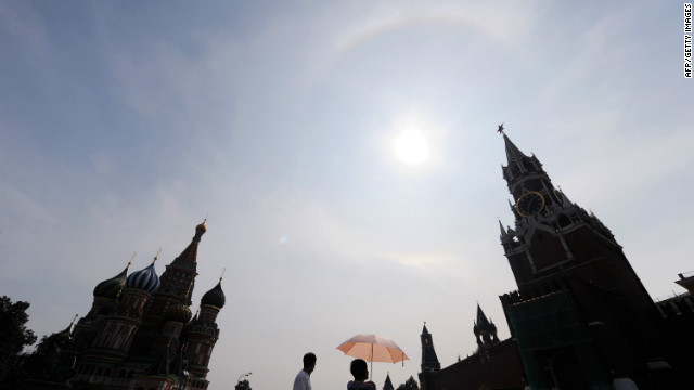 Russians walk near the Kremlin on Red Square under clear blue skies during a rare heat wave in Moscow, in August, 2010. According to a new report from the UK's Met Office, man-made climate change is likely to cause a global temperature rise of around 3-5C over the next century, and significantly increase instances of freak weather events.