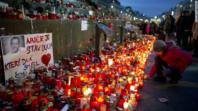 A girl lights a candle in Vaclavske Square in honor of Havel.