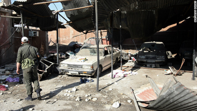 A Syrian soldier looks at cars wrecked by a blast at the Syrian General Intelligence headquarters in Damascus.