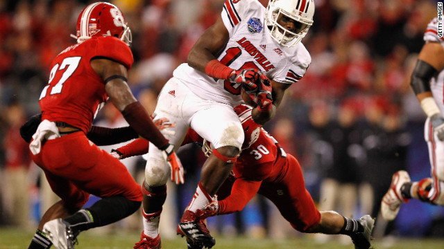 Dominique Brown of the Louisville Cardinals is tackled during the Belk Bowl.