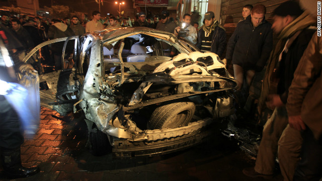 Palestinians look at a damaged car in Beit Lahia in northern Gaza after an Israeli airstrike on Tuesday.