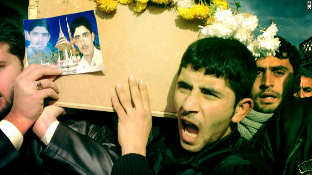 "A funeral procession takes place in Dar Kabir, Homs, for ""Malik,"" killed by government forces. His younger brother holds a photograph of Malik in his hands."