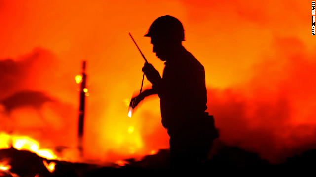 Myanmar rescue workers search for bodies from a large unexplained explosion and fire in Yangon on December 29, 2011.