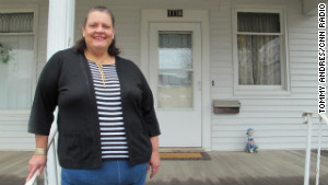 Kathy Potts stands on the front porch of her Cedar Rapids home where she plans to hang her Perry 2012 barn sign.