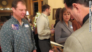 Aaron Rupp, meeting Rick Santorum for the ninth time, gets his book signed at Mitchell\'s party.