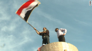 Dhirgham al-Zaidi, right, stands atop a pedestal that once held Saddam Hussein\'s statue as the Iraq flag is waved on Friday.