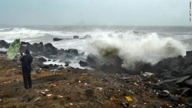 An Indian bystander looks at strong waves due to gusty winds in the wake of severe cyclonic storm 'Thane' at Marina Beach in Chennai on December 30, 2011. 