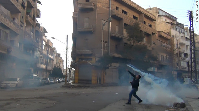 A protester in the flahspoint Syrian city of Homs throws a tear gas bomb back to security forces on December 27, 2011.