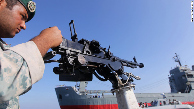 A soldier stands guard on a military speed boat during Iran's navy exercises in the Strait of Hormuz on December 28, 2011.