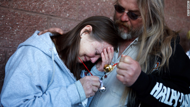 Safeway employee Sherrie Brown is comforted by Leroy Wood while participating in a ringing of the bells ceremony earlier Sunday. Several events were held to mark the one-year anniversary of the shooting at the La Toscana Village Safeway.