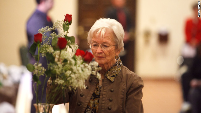During Sunday's memorial service, Teresa Bier makes a flower offering in honor of Christina Taylor-Green, a 9-year-old who was killed.