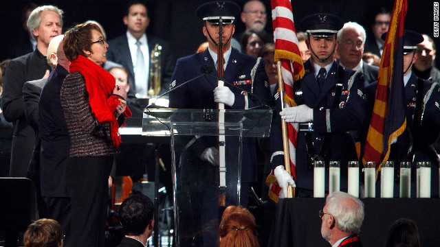 Rep. Gabrielle Giffords leads the crowd in the pledge of allegiance during a vigil on Sunday, January 8, 2012, in Tucson, Arizona, marking one year since a shooting rampage left her and 12 others wounded and six people dead.