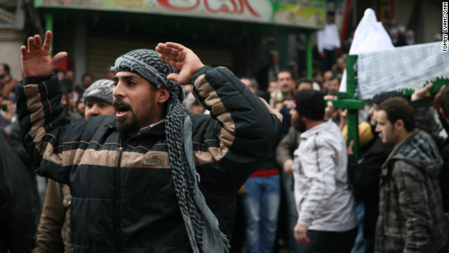 A protester chants as the body is carried though the streets of the neighborhood. 