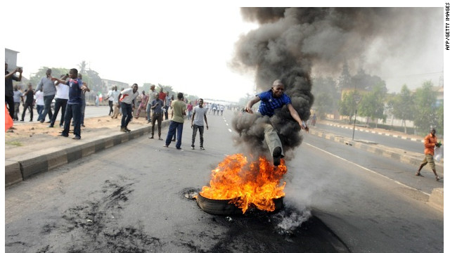 A boy jumping over a burning tyre on a street in Nigeria where protests against the removal of fuel subsidy have raged since 3 January.