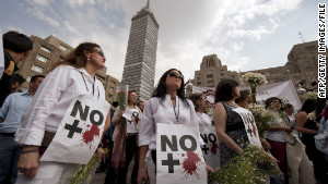 Anti-violence activists protest in Mexico City in April 2011. Their signs read, \