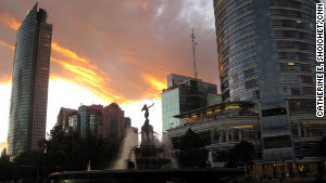 Towering buildings line Mexico City\'s Reforma Avenue. Once dogged by a crime-ridden reputation, the city is now a refuge.