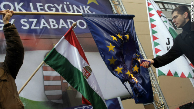 Member of the Hungarian Parliament and the Hungarian right-wing 'Jobbik' party, Elod Novak, right, sets an European Union flag on fire during a demonstration in Budapest on January 14, 2012.